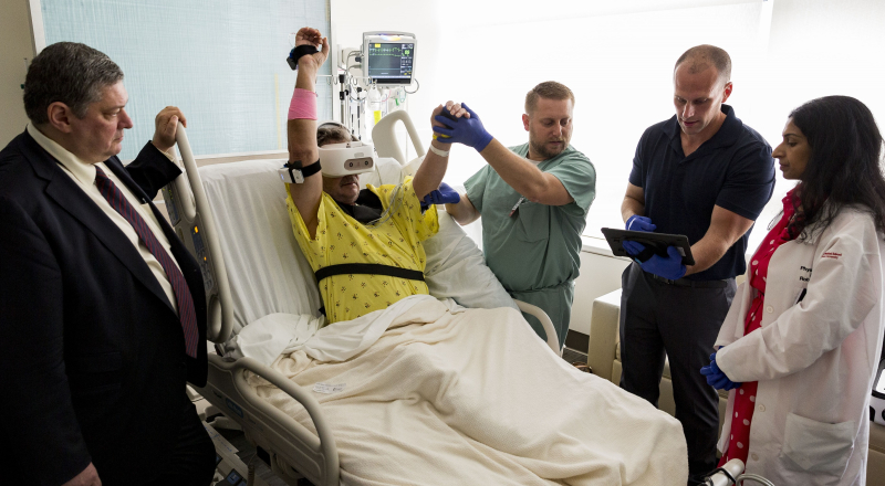 Stroke care -- patient using REAL Immersive system with members of care team